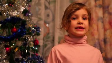 Girl stand near decorated christmas tree and says her wishes — Stock Video
