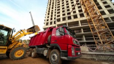 Excavator loads truck at construction site of living house — Stock Video