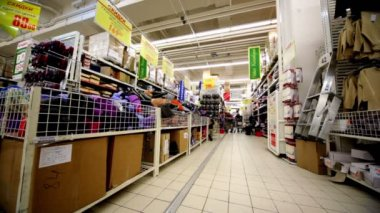 Few people walk among shelves with goods in hypermarket Auchan — Vídeo de stock