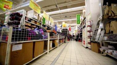 几人走在货架上,与大型超市欧尚的货物之间 — 图库视频影像