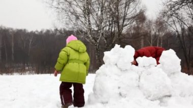 Mother with children play snowballs behind fortress — Stock Video