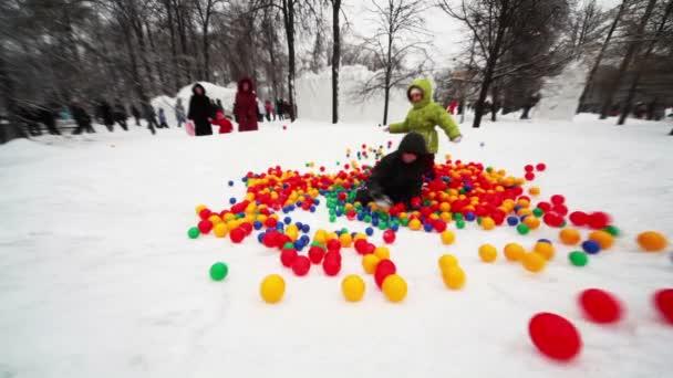 Niño y niña juegan en pila de bolas de colores en el parque — Vídeo de stock
