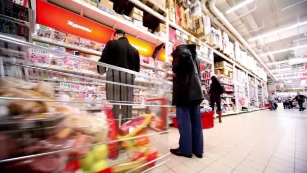 Plusieurs personnes choisissent des magazines sur la vitrine hypermarché auchan — Vidéo