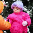 Little girl came and gives snow to another kid in pink down-padded coat — Stock Video
