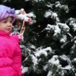 Girl stands and hold bow ribbon on Christmas tree covered with snow — Stock Video #29830479