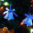 Stock Video: Two toy bells hang on Christmas tree among of blinking colored garlands
