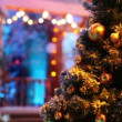 Stock Video: Christmas tree with balls stand in front of blurred house