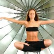 Stock Video: Young model sits with folded legs and hands raised, she meditates