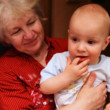 Stock Video: Grandmother hold baby in hands and smiling