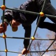 Stock Video: Kids climb on rope lattice at playground, closeup view from below