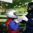 Stock Video: Carting trainer helps little boy to put on helmet