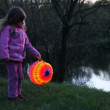Little girl hold ball from paper at night near lake — Stock Video #29831753