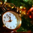 Stock Video: Alarm clock at three minutes remaining before New Years in front of festive lights Christmas tree