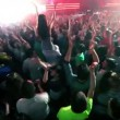 Girl sits on mans shoulders among people at rave party, DJ Armin VBuuren on stage — Stock Video #29831991