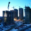 Stock Video: Workers at construction site in foreground of dormitory arecityscape