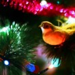 Stock Video: Yellow bird toy sits on Christmas tree among of blinking colored garlands