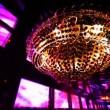 Stock Video: Chandelier and wall of monitors rhythmically flashing colored lights in nightclub