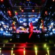 Stock Video: Two girls dancing on platforms in nightclub with monitors walls