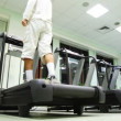 Stock Video: Man stand at treadmill in gym, he turn on and begins go