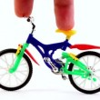 Stock Video: Fingers on toy bike, rotates handlebars, and then ride away