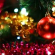 Stock Video: Glass toy red ball hangs on Christmas tree among of blinking garlands