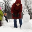 Mother make hands for snowman with two children — Stock Video #29832541