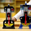 Man rotates each of two models of internal combustion engine on desk — Stock Video
