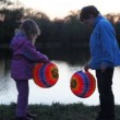 Little boy and girl hold colorful ball from paper at night — Stock Video #29833023