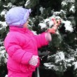 Little girl shake bow ribbon on Christmas tree covered with snow — Stock Video