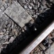 Stock Video: Rails and cross ties of railway among stones, shown in motion
