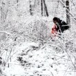 Stock Video: Mother walk with her kid in bush on woods where all covered with snow