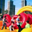 Vídeo de stock: Kids jump on inflated playground at stadium Yantar