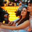 Stock Video: Couple sits embracing near snowy Christmas trees and blinking lamps