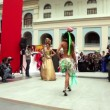 Models in costumes with large uncommon hairdo walk on podium — Stock Video
