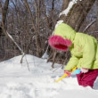Stock Video: Little girl in winter coat snow shovel digs and throws it up