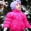 Little girl stands and look toward in front of Christmas tree covered with snow — Stock Video