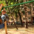 Stock Video: Boy and little girl sway on swing at playground