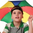 Boy in cap as umbrellrainbow colors fun pretend that hiding from rain — Stock Video #29834829