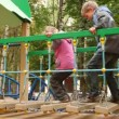 Stock Video: Little girl and boy jump hang down steps on playground