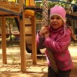Stock Video: Little girl hangs on rope at playground and sway