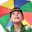 Stock Video: Boy in cap as umbrellrainbow colors happily smiles