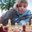 Boy plays wooden chess in park, people walk around — Stock Video #29834993