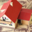 Toy house with red tiled roof on dollars bank notes — Stock Video #29835041