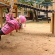 Stock Video: Little girl sway on rope at playground
