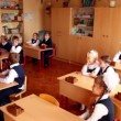 Schoolchildren sits in classroom, one boy show digital game to his classmates — Vídeo Stock