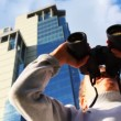 Inquisitive boy looks through binoculars on background of skyscrapers, then turns — Stock Video