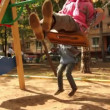Brother and little sister sway on swing at playground — Stock Video #29835095