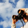 Stock Video: Inquisitive boy looks through binoculars against sky with clouds