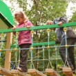 Stock Video: Little girl and boy sway on hang down steps at playground