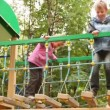 Stock Video: Little girl and boy rock on hang down steps at playground